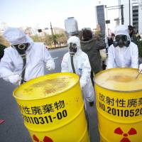 Protesters in hazmat suits beat barrels bearing nuclear waste symbols during a demonstration in Tokyo on March 9. | AP