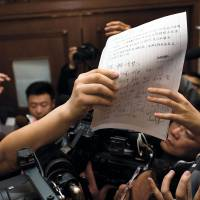 A letter signed by Chinese relatives of passengers on Malaysia Airlines Flight MH370 is shown to media Sunday in Beijing. | AP