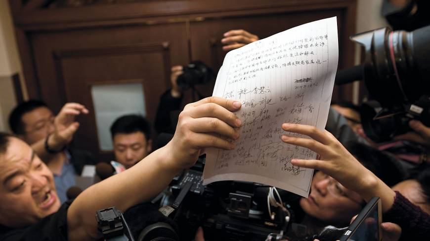 A letter signed by Chinese relatives of passengers on Malaysia Airlines Flight MH370 is shown to media Sunday in Beijing.