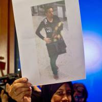 A Malaysian official displays a photo of one of two men who boarded missing Malaysia Airlines flight MH370 using stolen passports, in Kuala Lumpur on Tuesday.   AFP-JIJI