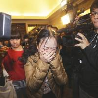 A relative of a Malaysia Airlines flight MH370 passenger breaks down in Beijing on Sunday. | REUTERS