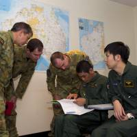Australian military officers discuss a plan with Maritime Self-Defense Force Lt. Cmdr. Takayuki Kanemori during a briefing on the search for Malaysia Airlines Flight MH370 on Thursday at a Royal Australian Air Force base in Bullsbrook, Western Australia. | AFP-JIJI
