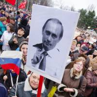 A protester holds a placard showing Russian President Vladimir Putin during a rally in support of Moscow in the Ukrainian city of Odessa on Sunday. | AFP-JIJI