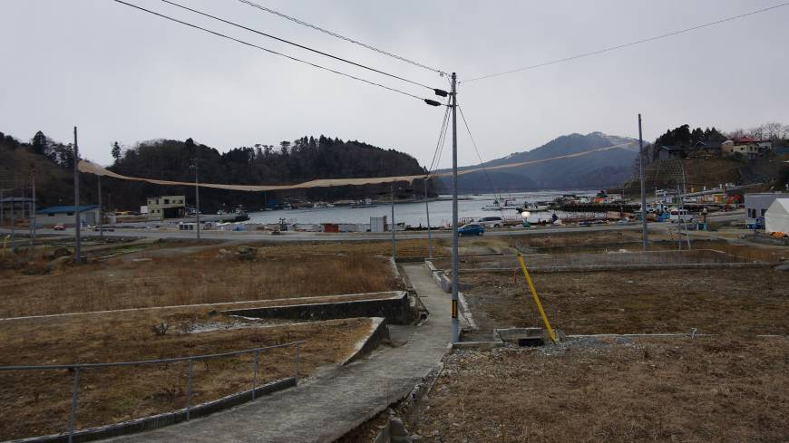 An orange banner is hung at the height of a 9.9-meter seawall that the Miyagi Prefectural Government plans to build to block possible tsunami at Kesennuma's Shibitachi fishery port on Feb. 25. Many housing lots, destroyed by tsunami three years ago, are still empty.