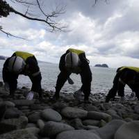Police in Ishinomaki, Miyagi Prefecture, on Tuesday continue searching for the remains of people missing in the March 11, 2011, tsunami. | AP