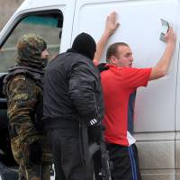 Armed men claiming to be members of Ukraine's disbanded Berkut riot police force and local militiamen on Friday search a driver at a checkpoint on a highway connecting the Crimean Peninsula to the rest of the country. | AFP-JIJI