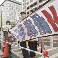Antinuclear activists display a banner to protest reactor restarts at the Sendai nuclear power plant in Kagoshima Prefecture during a rally Thursday in Tokyo. | KYODO