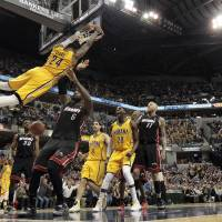 Fun and games: The Pacers' Paul George hangs on the rim after dunking against the Heat on Wednesday in Indianapolis. The Pacers won 84-83. | AP