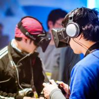 BitSummit attendees try out games made for the Oculus Rift virtual-reality headset such as 'Project life.'  | DYLAN CUTHBERT