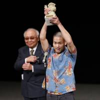 Director Hiroshi Shinagawa holds up his Golden Shisha Award.  | OKINAWA INTERNATIONAL MOVIE FESTIVAL / YOSHIMOTO LAUGH & PEACE