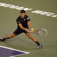 Right back at you: Novak Djokovic hits a return against Victor Hanescu during their match in the second round of the BNP Paribas Open on Sunday. Djokovic won 7-6 (7-1), 6-2. | AP