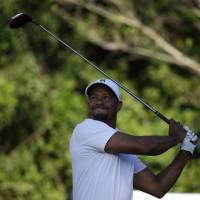 In the hunt: Tiger Woods watches his tee shot on the third hole during the third round of the Honda Classic on Saturday. Woods fired a 65 and is seven shots off the pace. | AP