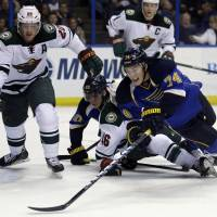 Fire on ice: The Blues' T.J. Oshie vies for the puck against a group of Wild players on Thursday. Oshie had a hat trick in the win. | AP