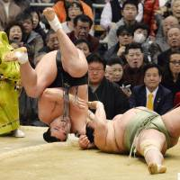 Evasive action: Yokozuna Harumafuji (left) rolls out of the ring after throwing Toyonoshima to the ground on the first day of the Spring Grand Sumo Tournament in Osaka on Sunday. | KYODO