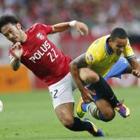 Punished: Yuki Abe (left) and Urawa once hosted Theo Walcott and Arsenal in Saitama, but will suffer the indignity of playing a home match in an empty stadium on March 23. | AP