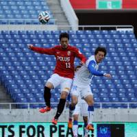 No fans allowed: Urawa's Keita Suzuki (left) vies for the ball with Shimizu S-Pulse's Mitsunari Musaka at an empty Saitama Stadium on Sunday. The match ended in a 1-1 draw. | AFP-JIJI