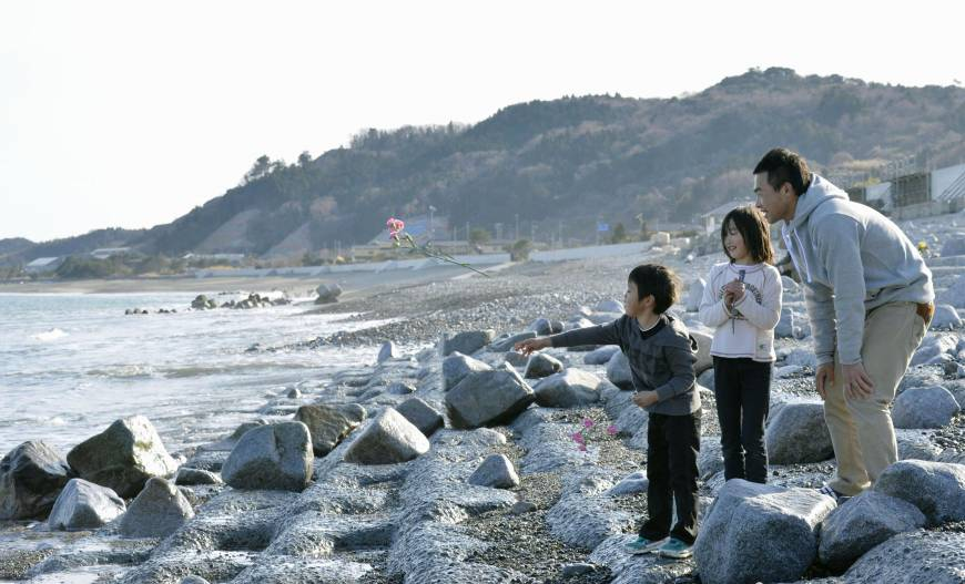 Subaru Niizuma, 6, accompanied by his sister Shizuku, 8, and father Atsushi, 40, throws a pink flower into the ocean in Iwaki, Fukushima Prefecture, on Sunday in honor of his grandmother, who died in the March 11 tsunami and was fond of pink flowers.