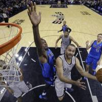 Back in style: Spurs guard Tony Parker goes in for a layup against the Mavericks' Samuel Dalembert during their game on Sunday in San Antonio. The Spurs defeated their in-state rivals from Dallas 112-106. | AP