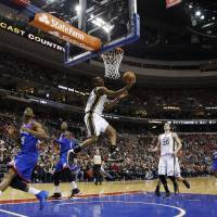 Up and under: Utah's Alec Burks goes up for a reverse layup against Philadelphia in the second half on Saturday night. | AP