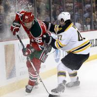 Ice shower: New Jersey's Patrik Elias moves for the puck against Boston's Torey Krug in the second period on Tuesday night. The Bruins beat the Devils 4-2. | AP