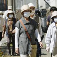 Elderly people wearing masks walk through the streets of Satsumasendai, Kagoshima Prefecture, in 2013. | KYODO