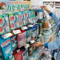 A pharmacy employee restocks hay fever products in April 2009. | KYODO