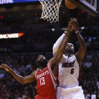 That's mine: Rockets guard James Harden (left) and the Heat's LeBron James vie for a rebound on Sunday in Miami. | AP