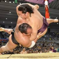 Close combat: Endo (right) takes down Osunaarashi at the Spring Grand Sumo Tournament in Osaka on Sunday. | KYODO
