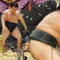 Still in the hunt: Kakuryu (left) stands in the ring after beating Takayasu at the Spring Grand Sumo Tournament on Monday. | KYODO