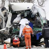 Police probe what originally was the front of an overnight bus Monday after it rammed two parked trucks at a rest area along the Hokuriku Expressway in Oyabe, Toyama Prefecture.   KYODO