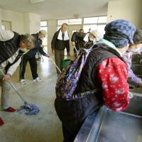 Evacuees from Futaba, Fukushima Prefecture, clean up on Friday the high school gym in Kasu, Saitama Prefecture, that had served as the last evacuation shelter for victims of the 2011 Fukushima No. 1 meltdown crisis. | KYODO
