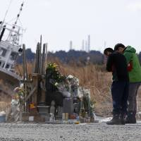People in Namie, Fukushima Prefecture, pray Tuesday for victims of the March 11, 2011, earthquake and tsunami as Tokyo Electric Power Co.'s stricken Fukushima No. 1 nuclear plant can be seen in the far distance. | REUTERS