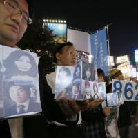 Holding photos of suspected abduction victims, people stage a rally in Tokyo last September calling on the government to take action against North Korea. | KYODO