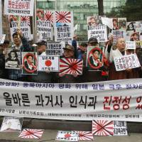 Protesters hold up defaced Rising Sun flags and portraits of Prime Minister Shinzo Abe as they celebrate Independence Movement Day in Seoul on Saturday. | AP