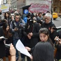 Anti-nuclear activists stage a protest surrounded by members of the media Tuesday in front of the Japanese Consulate General in New York. | KYODO