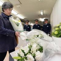 Shizue Takahashi, widow of deputy stationmaster Kazumasa Takahashi, adds a bouquet to the offering of flowers for sarin gas attack victims at the 19th annual memorial ceremony Thursday in Kasumigaseki Station in Chiyoda Ward, Tokyo. | POOL