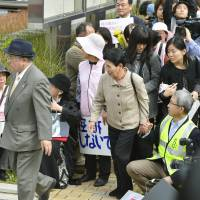 Hideko Hakamada, 81 (center), and a lawyer for her brother, Iwao Hakamada, enter the Shizuoka District Court Thursday. | KYODO