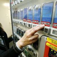 A woman in Minato Ward, Tokyo, points to a sticker on a tobacco vending machine that shows the price of a pack of Mevius cigarettes will be raised from ¥410 to ¥430 on Tuesday, in line with the consumption tax hike. | KYODO