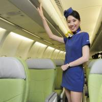 A cabin attendant for Skymark Airlines poses in a new blue miniskirt uniform that's causing waves in the industry. | KYODO