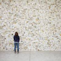 "Moving images: A woman contemplates a wall of photos during the exhibition ""From Tsunami, Photographs, and Then: Lost & Found Project."" 