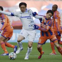Got you surrounded: Gamba Osaka's Yasuhito Endo (left) takes on the Albirex Niigata defense during Gamba's 2-0 win on Saturday. | KYODO