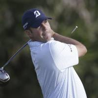 Eye of the storm: Matt Kuchar hits from the eighth tee at the Cadillac Championship in Doral, Florida, on Friday. | AP