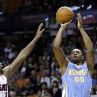Cool down: Nuggets forward Darrell Arthur shoots as the Heat's Chris Bosh defends on Friday in Miami. The Nuggets won 111-107. | AP