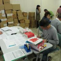 Volunteers sort out books donated by well-known children's book author Taro Gomi in Ota Ward, Tokyo, last April. | KYODO