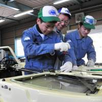 Minoru Ishikawa (center), an adviser to automobile equipment maker Shinmei Industry Co., teaches students how to affix a door to an old Toyota Publica car during a class in Toyota, Aichi Prefecture, in February. | CHUNICHI SHIMBUN