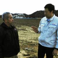 Yoshinori Koreeda (right) of Kagome Co. talks with Toshiro Abe of the Agriead Naruse agricultural firm. | CHUNICHI SHIMBUN