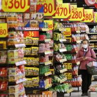 A customer browses through a riot of sale price signs at a Seiyu GK supermarket in Tokyo on March 13. | BLOOMBERG