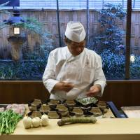 Yoshihiro Murata (center), master chef at Kikunoi and chairman of the Japanese Culinary Academy, cooks at the restaurant during a media tour arranged by the Foreign Press Center/Japan in Tokyo on Dec. 11.  | BLOOMBERG
