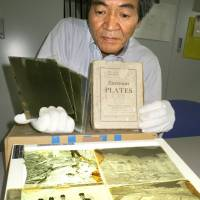 Local meteorological official Shozo Fujiwara holds some of the glass-plate negatives recording the 1896 disasters.  | KYODO