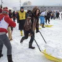 Participants scoop and carry snow in an international competition on snow shoveling held in Otaru, Hokkaido, in January. | KYODO